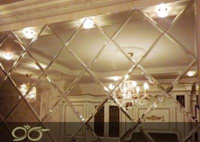 آینه تراش خورده لوزی نصب شده روی دیوار سالن