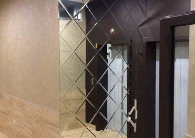 آینه تراش خورده لوزی نصب شده کنار درب ورودی